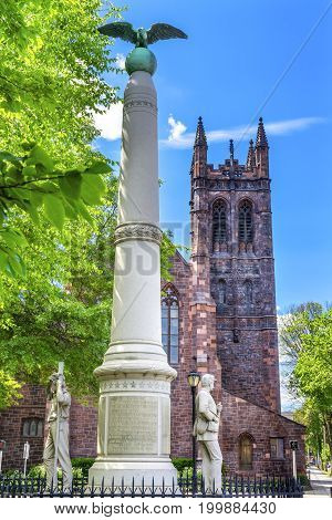 NEW HAVEN, CONNECTICUT-JUNE 24, 2017 Eagle Topped Pillar Broadway Civil War Monument Christ Church New Haven Connecticut. Dedicated in 1905 to Four Connecticut Civil War Regiments. Christ Church built in 1895.