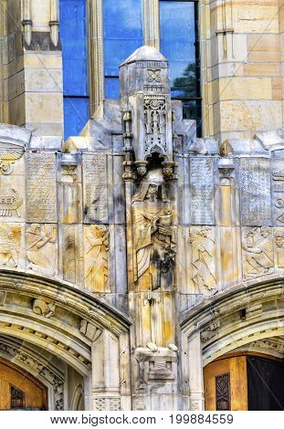 NEW HAVEN, CONNECTICUT-JUNE 24, 2017 Statue Sculptuee Door Yale University Sterling Memorial Library Statue New Haven Connecticut Fifth largest library in the United States