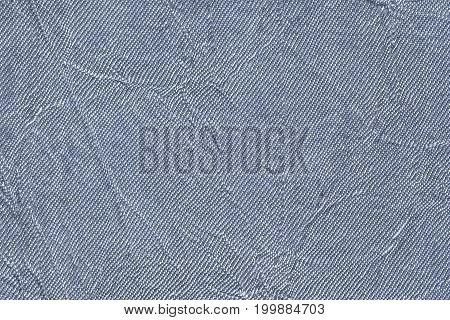Light blue wavy background from a textile material. Fabric with fold texture closeup. Creased shiny denim cloth.