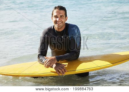 Surfer in wetsuit leaning on surfboard smiling