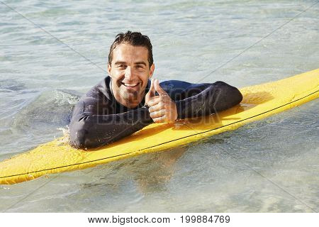 Portrait of surfer with thumbs up on surfboard smiling