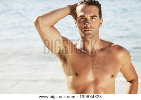 Handsome shirtles dude posing on beach portrait