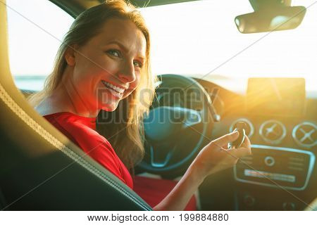Happy woman in a red dress with a key in her hand is sitting in the car. The concept of buying or renting a car