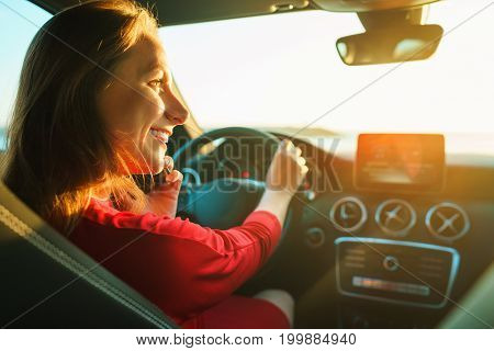 Happy woman in red dress driving car. The concept of buying or renting a car