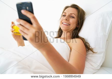 Cute woman wakes up and checks the smartphone and drinks orange juice in bed in the morning