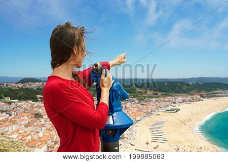 Beautiful female tourist using coin paid binoculars on high hill and looking at cityscape of Nazareth Portugal