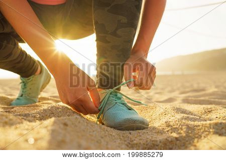 Running shoes - woman tying shoe laces. Closeup of female sport fitness runner getting ready for jogging on sandy beach at sunset