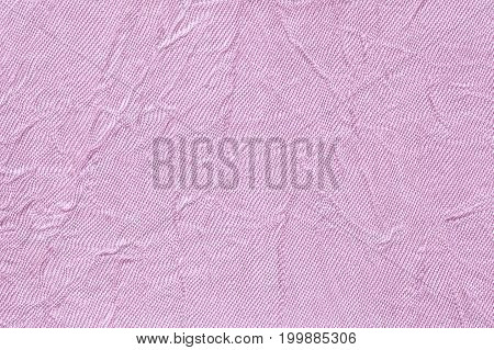 Light violet wavy background from a textile material. Fabric with fold texture closeup. Creased shiny lilac cloth.