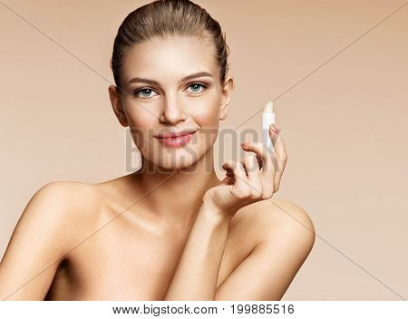 Young woman with hygienic lipstick looks at camera. Photo of attractive woman on beige background. Youth and skin care concept