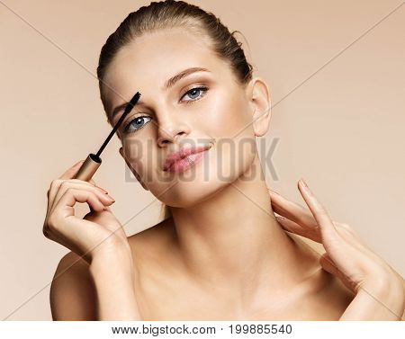 Beautiful woman applying eyebrow brush with gel. Portrait of woman finishing her makeup on beige background. Perfect makeup