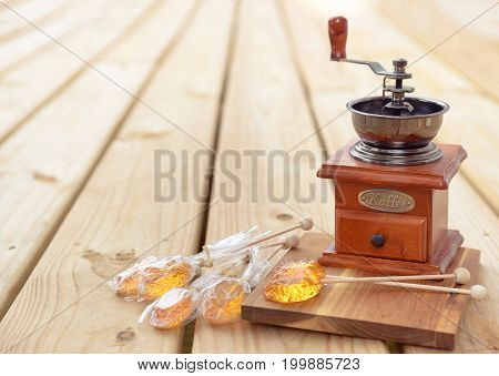 Honey caramel candy lollipop with sticks and vintage coffee mill on wooden background. Products display, view.