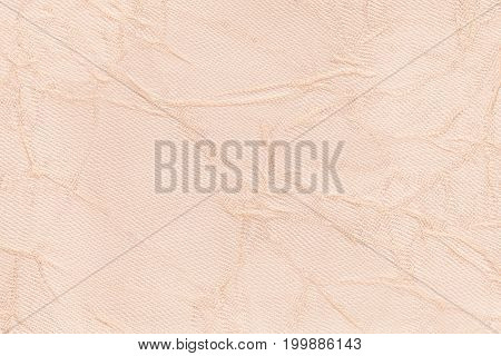 Light beige wavy background from a textile material. Fabric with fold texture closeup. Creased shiny cream cloth.