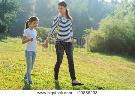 Pleasant weekend. Charming slender woman holding a hand of her adorable daughter while having a walk with her in the park