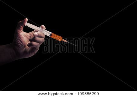 The Doctor's an medical syringe injection in hand palm or fingers. Liquid drug or narcotic. on black background with copy space. Medical part concept.