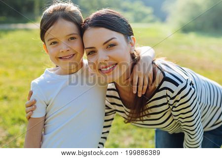 Happy family. Adorable little girl and her pretty young mother hugging each other and smiling at the camera broadly during a walk in the park