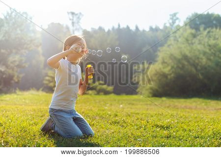 Lovely weekend. Petite little girl standing on her knees in the middle of a sun-drenched meadow and blowing soap bubbles