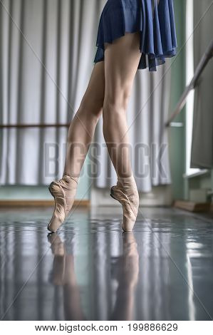 Harmonic legs of a ballet dancer in a blue dance wear who stands on pointes next to the ballet barre. She wears beige pointe shoes. Her feet reflected in the glossy floor. Closeup. Vertical.