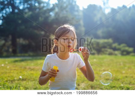 Having good time. The close up of a beautiful little girl sitting in the park meadow and blowing soap bubbles