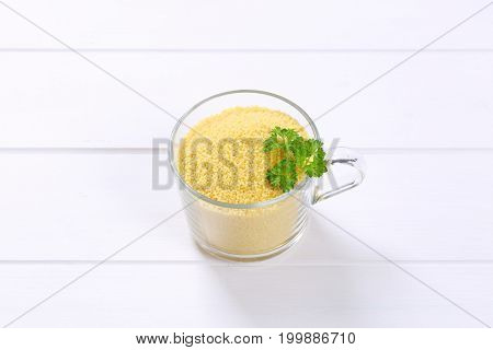 cup of raw couscous on white wooden background