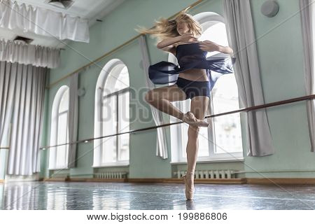 Beautiful ballerina is posing in a motion in the ballet hall opposite large arch windows. She is circling on the left leg. Girl wears a dark dance wear and beige poine shoes. Horizontal.