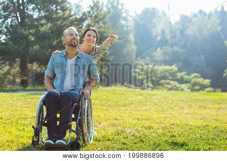 Look there. Pleasant young woman standing behind her incapacitated husband in a wheelchair and pointing at something in the distance