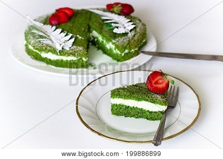 One Piece Of Green Spinach Cake With Butter Cream And Strawberry On White Plate. Selective Focus