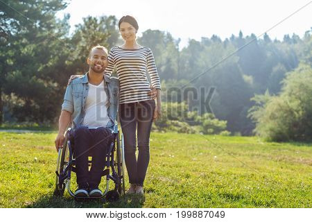 Happy couple. Charming young woman hugging her pleasant husband in a wheelchair, both of them posing for the camera in the meadow, smiling pleasantly