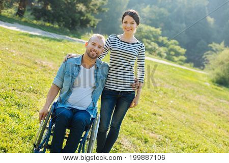 Limitless love. Pretty young woman standing next to her pleasant husband with disabilities sitting in a wheel chair, both of them posing for the camera in the park