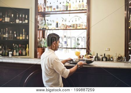 Waiter serving at the bar of the hotel