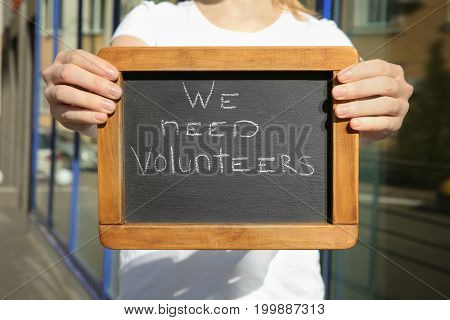 Woman holding little chalkboard with text WE NEED VOLUNTEERS outdoors, closeup