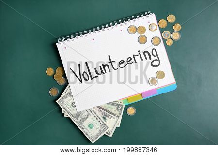Notebook with word VOLUNTEERING and money on green chalkboard