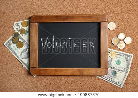 Little chalkboard with word VOLUNTEER and money on cork background