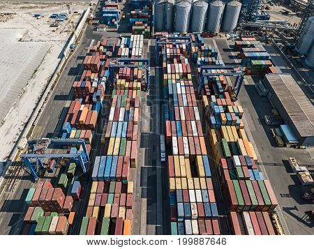 Large warehouse with many multicolored containers. There are cranes, trucks, technical buildings. Top view panoramic photo. Outdoors.