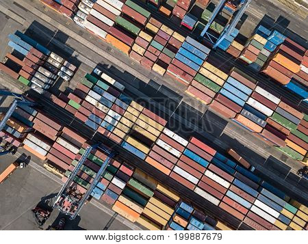 Top view at the warehouse with many multicolored containers. There are cranes and trucks. Horizontal photo. Outdoors.
