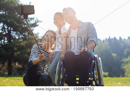 Happiest family. Pleasant cheerful mother standing near her husband in a wheelchair together with her daughter and taking a selfie with the help of a selfie stick