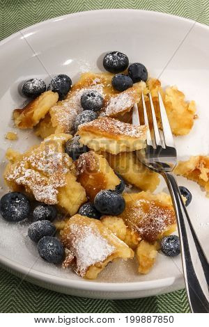 home baked kaiserschmarrn with blueberries sprinkled with powdered sugar