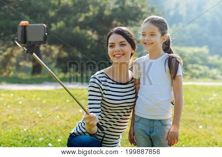 Gathering memories. Loving young mother squatting near her little daughter, hugging her and taking a selfie with a monopod
