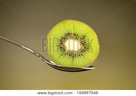 Sliced fresh and juicy green kiwi fruit on spoon with yellow light background for healthy food and fruit salad concept