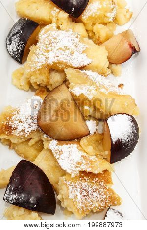 home baked kaiserschmarrn with plums sprinkled with powdered sugar
