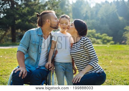 Pure affection. Tender young mother and loving young father with mobility impairment kissing their little daughter on both cheeks while the girl closing her eyes tight