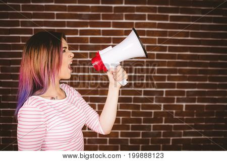 Woman shouting on megaphone against brick wall