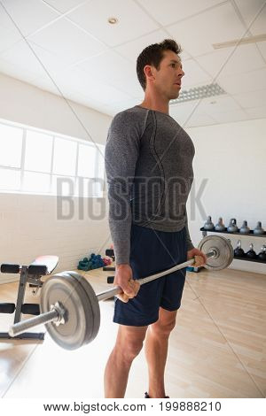 Male athelte looking away while lifting barbell at gym