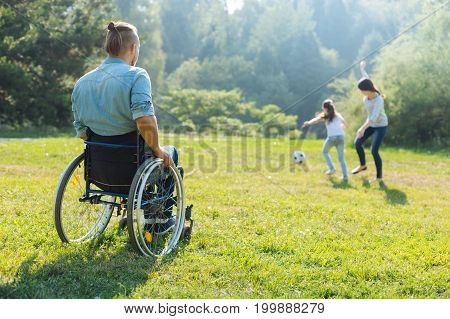 Active weekend. Back view of a young man in a wheelchair sitting in the meadow and watching his beloved wife and daughter playing football