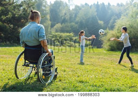 Energetic weekend. Handsome young man with disabilities sitting in a wheelchair and watching his daughter and wife throwing a ball to each other during a walk in the park