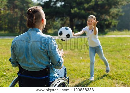 Amusing game. Back view of a young man in a wheelchair catching a ball thrown by his little girl and enjoying the weekend in the park