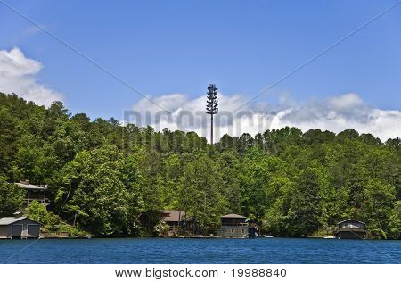 A cell tower high above the tree line over homes and a lake. poster