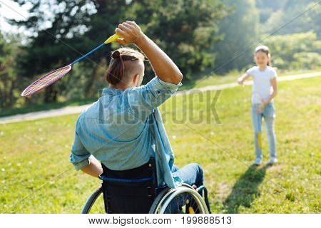 Enjoying badminton. Back view of a young man with mobility impairment holding a racquet and being ready to pass a shuttlecock to his daughter