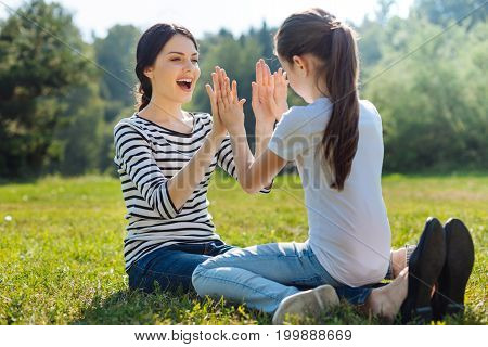 Lovely bonding. Overjoyed young woman sitting on the grass in the meadow and playing pat-a-cake game with her daughter sitting on her lap while smiling happily