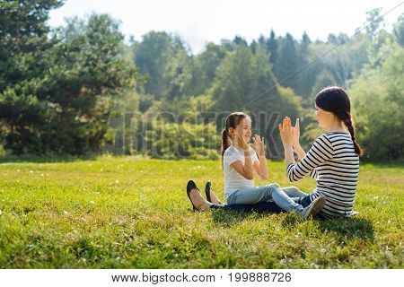 Laid-back weekend. Gorgeous young woman holding her little daughter in her lap and playing pat-a-cake with her while sitting in the sun-drenched meadow