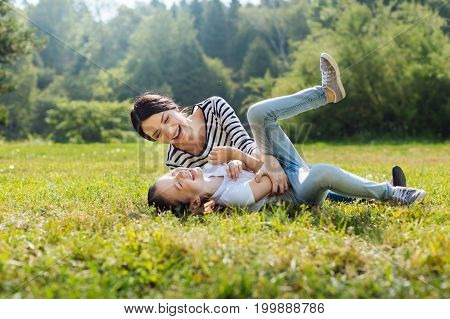 Joyful mood. Happy charming woman goofing around with her little daughter while lying on the grass in the sun-drenched park meadow